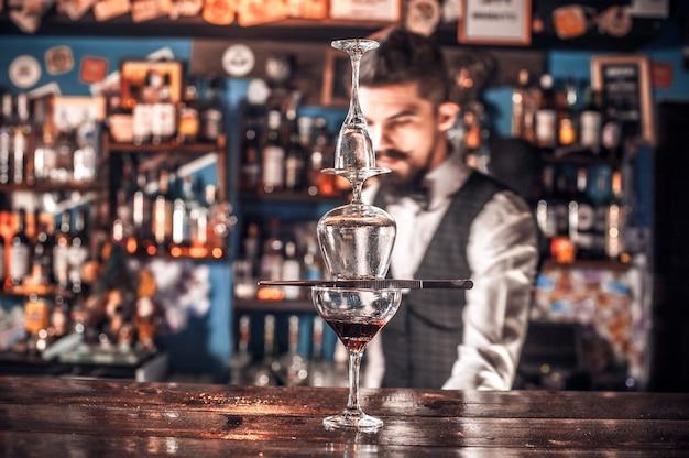 Selbstbewusster barkeeper, der frisches alkoholisches getränk in die gläser in der kneipe gießt