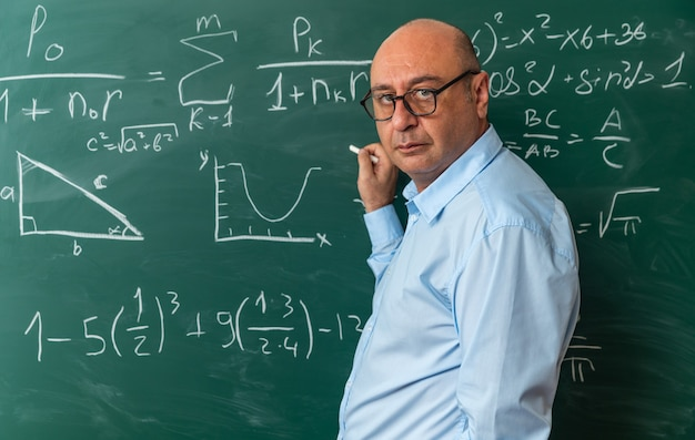 Selbstbewusster blick auf den vorderen männlichen lehrer mittleren alters mit brille, der vor der tafel steht