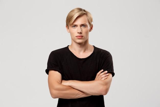 Selbstbewusster blonder hübscher junger mann, der schwarzes t-shirt mit auf der brust gekreuzten händen trägt