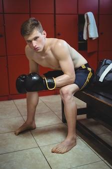 Selbstbewusster boxer, der mit boxhandschuhen sitzt