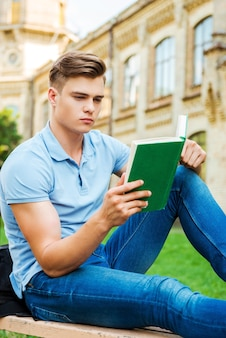Selbstbewusster bücherwurm. selbstbewusster männlicher student liest ein buch, während er auf der bank und vor dem universitätsgebäude sitzt