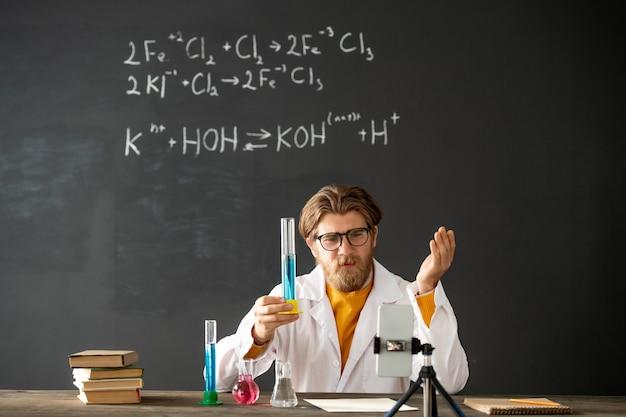 Selbstbewusster chemielehrer in freizeitkleidung, der seinem online-publikum eine flasche mit blauer flüssigkeit zeigt, während er im unterricht seine eigenschaften erklärt