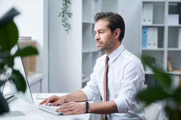 Selbstbewusster direktor der unternehmensorganisation, der in seinem büro vor dem computermonitor sitzt