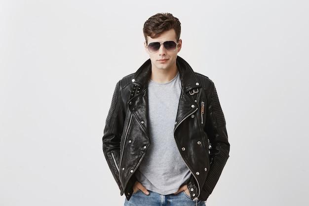 Selbstbewusster ernsthafter gutaussehender mann trägt schwarze lederjacke über grauem t-shirt und stilvoller brille, schaut direkt in die kamera, isoliert. menschen- und stilkonzept