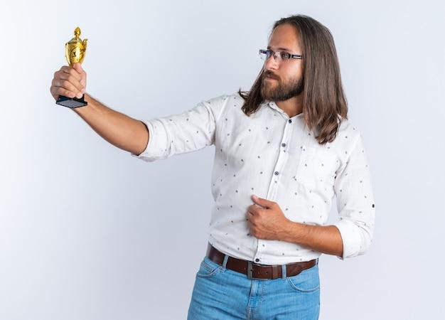 Selbstbewusster erwachsener, gutaussehender mann mit brille, der die hand auf dem bauch hält, sich ausstreckt und den gewinnerpokal isoliert auf weißer wand betrachtet