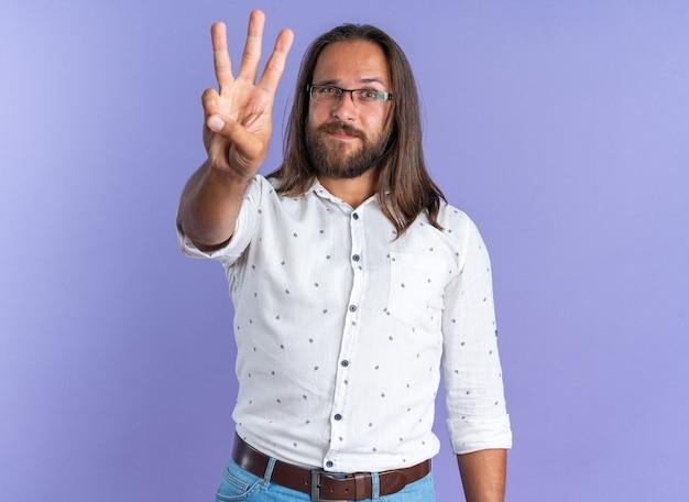 Selbstbewusster erwachsener, gutaussehender mann mit brille, der die kamera anschaut, die drei mit der hand isoliert auf lila wand zeigt