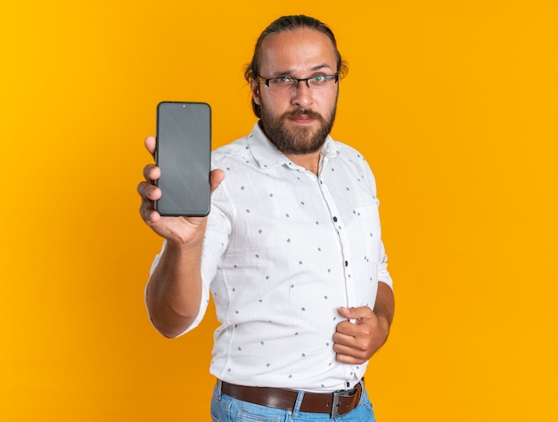 Selbstbewusster erwachsener, gutaussehender mann mit brille, der in der profilansicht steht und die hand auf dem bauch hält und in die kamera schaut, die das mobiltelefon isoliert auf der orangefarbenen wand zeigt