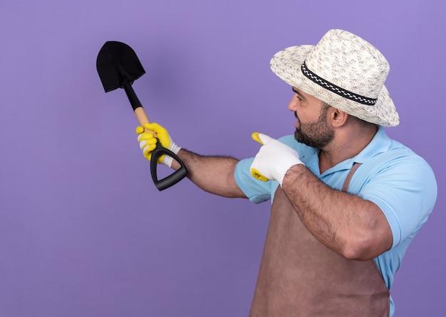 Selbstbewusster erwachsener kaukasischer männlicher gärtner mit gartenhut und handschuhen, der auf spaten schaut und zeigt