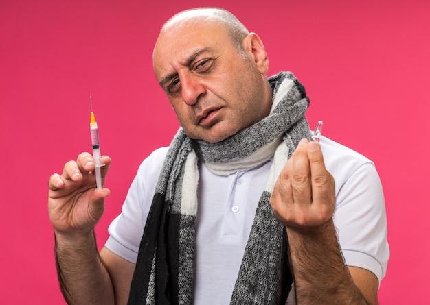 Selbstbewusster erwachsener kranker kaukasischer mann mit schal um den hals, der spritze und ampulle isoliert auf rosa wand mit kopierraum hält