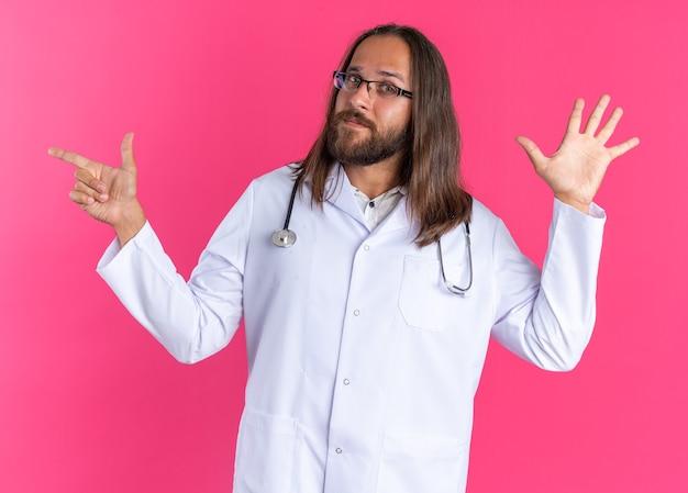 Selbstbewusster erwachsener männlicher arzt, der ein medizinisches gewand und ein stethoskop mit einer brille trägt, die fünf auf die seite zeigt