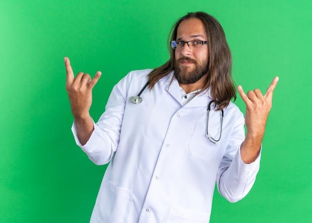 Selbstbewusster erwachsener männlicher arzt, der medizinisches gewand und stethoskop mit brille trägt, die felsenzeichen macht