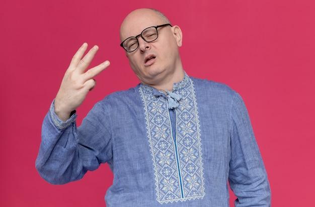 Selbstbewusster erwachsener mann im blauen hemd mit brille, der drei mit den fingern gestikuliert