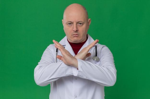 Selbstbewusster erwachsener mann in arztuniform mit stethoskop, das die hände kreuzt und kein zeichen gestikuliert