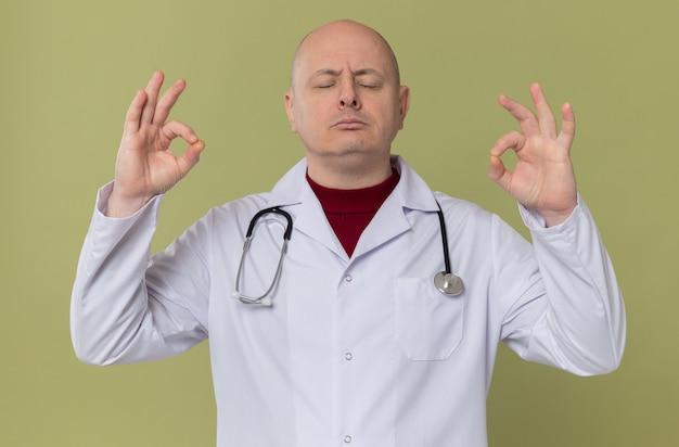 Selbstbewusster erwachsener mann in arztuniform mit stethoskop, der mit geschlossenen augen meditiert