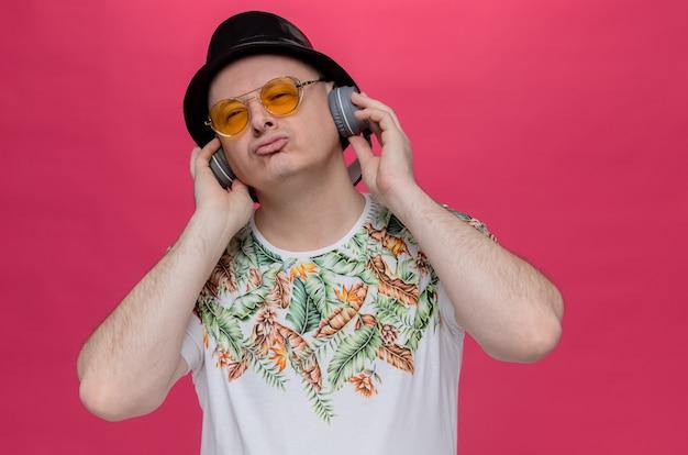 Selbstbewusster erwachsener mann mit sonnenbrille auf kopfhörern, der einen schwarzen zylinder trägt und zur seite schaut