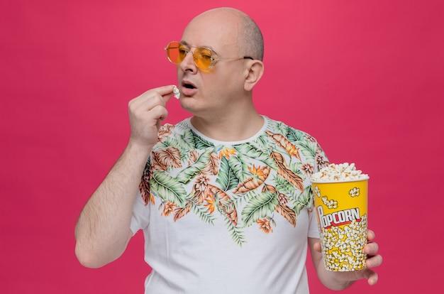 Selbstbewusster erwachsener mann mit sonnenbrille, der popcorn-eimer hält