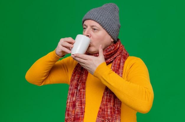Selbstbewusster erwachsener mann mit wintermütze und schal um den hals, der aus der tasse trinkt und auf die seite schaut