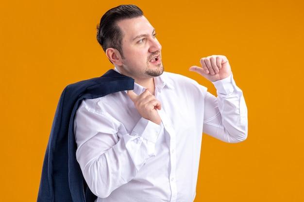 Selbstbewusster erwachsener slawischer geschäftsmann, der eine jacke auf seiner schulter hält und auf die seite schaut