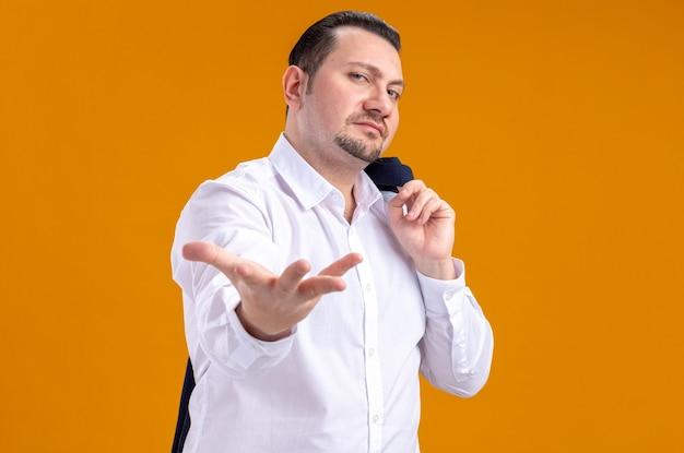 Selbstbewusster erwachsener slawischer geschäftsmann, der jacke auf seiner schulter hält und die hand offen hält