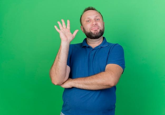 Selbstbewusster erwachsener slawischer mann, der fünf mit der hand lokalisiert auf grüner wand mit kopienraum zeigt