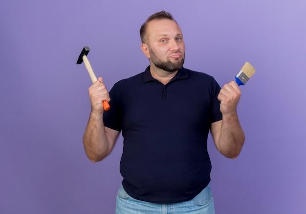 Selbstbewusster erwachsener slawischer mann, der hammer und pinsel isoliert hält