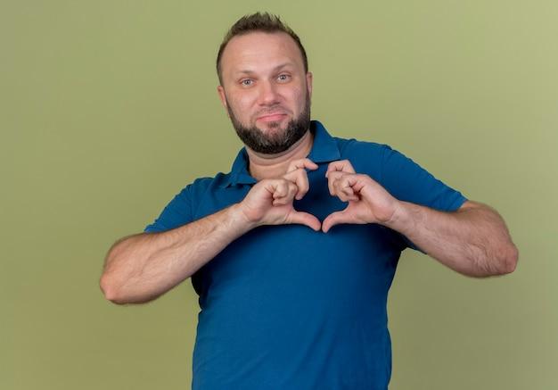 Selbstbewusster erwachsener slawischer mann, der herzzeichen tut