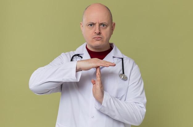 Selbstbewusster erwachsener slawischer mann in arztuniform mit stethoskop, das auszeitzeichen gestikuliert