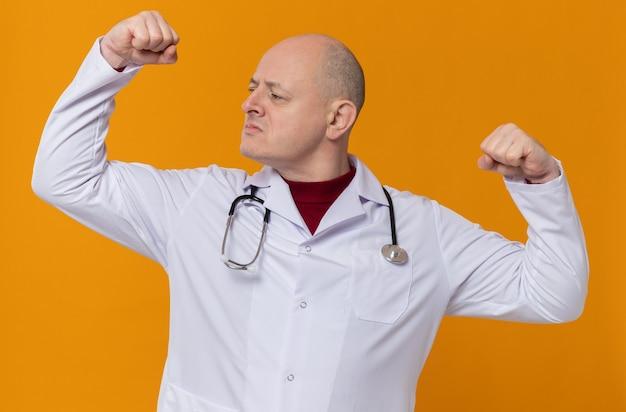 Selbstbewusster erwachsener slawischer mann in arztuniform mit stethoskop, das seinen bizeps anspannt und zur seite schaut