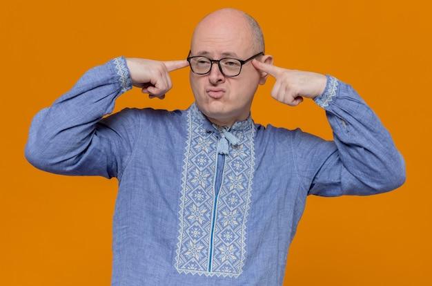 Selbstbewusster erwachsener slawischer mann in blauem hemd und mit optischer brille, der die finger an die schläfen legt und zur seite schaut