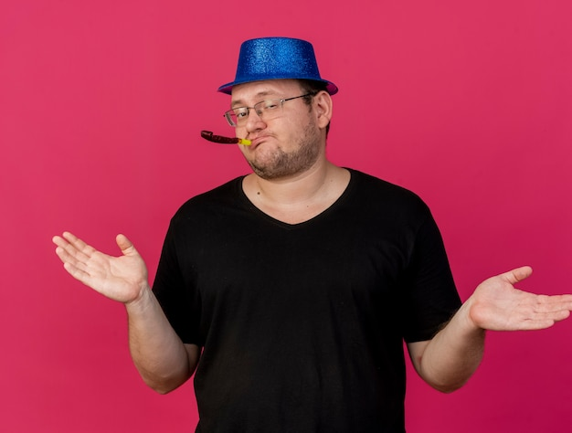 Selbstbewusster erwachsener slawischer mann in optischer brille mit blauem partyhut, der die hände offen hält und partypfeife bläst