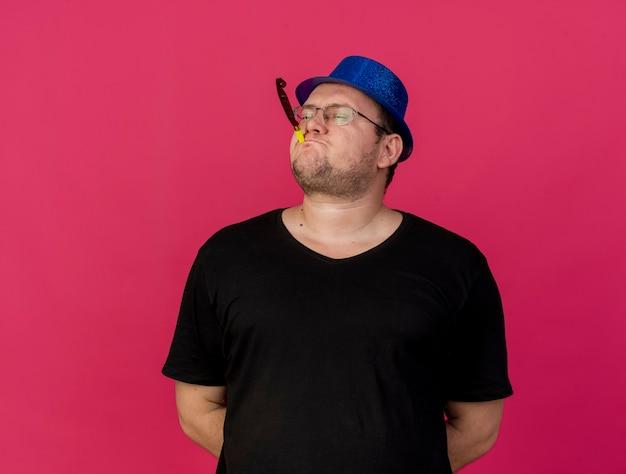Selbstbewusster erwachsener slawischer mann in optischer brille mit blauem partyhut, der partypfeife bläst