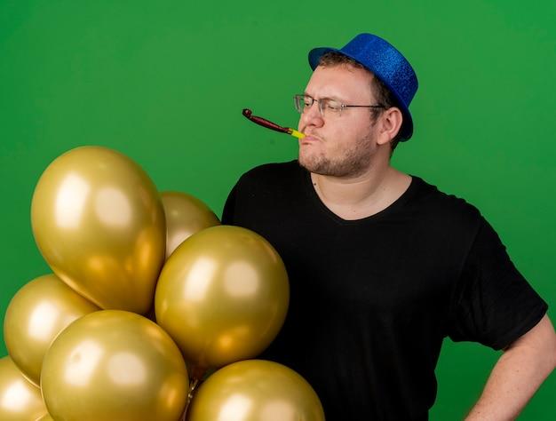 Selbstbewusster erwachsener slawischer mann in optischer brille mit blauem partyhut hält heliumballons, die pfeife auf die seite schauen