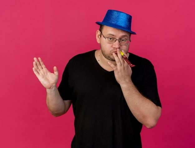 Selbstbewusster erwachsener slawischer mann in optischer brille mit blauem partyhut steht mit erhobener hand, die partypfeife bläst