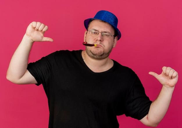 Selbstbewusster erwachsener slawischer mann in optischer brille mit blauem partyhut zeigt auf sich selbst mit zwei händen, die partypfeife blasen
