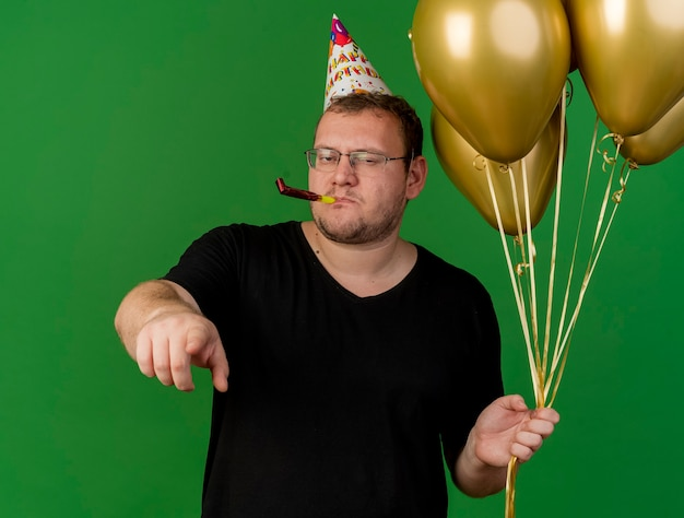 Selbstbewusster erwachsener slawischer mann in optischer brille mit geburtstagskappe hält heliumballons, die partypfeife blasen und auf die kamera zeigen