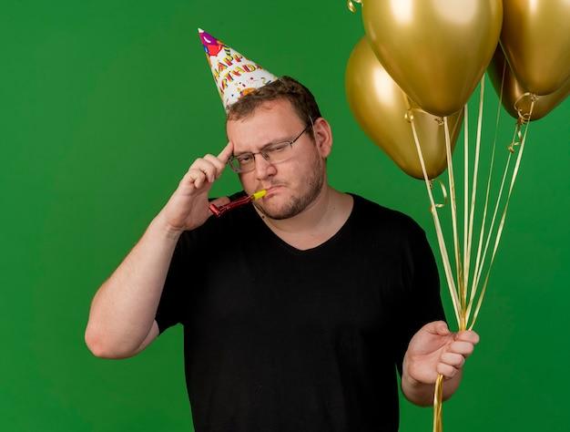 Selbstbewusster erwachsener slawischer mann in optischer brille mit geburtstagskappe legt den finger auf die schläfe und hält heliumballons, die partypfeife blasen