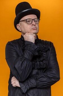 Selbstbewusster erwachsener slawischer mann mit hut und optischer brille in schwarzem gothic-hemd, der die hand auf sein kinn legt und zur seite schaut
