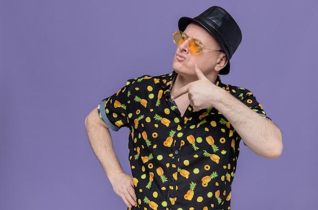 Selbstbewusster erwachsener slawischer mann mit schwarzem hut mit sonnenbrille, der auf die seite schaut und zeigt