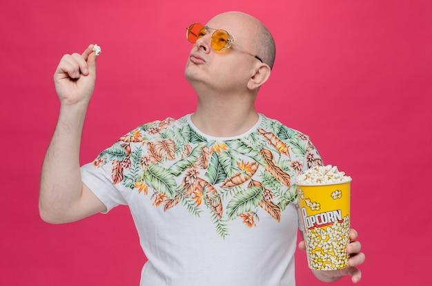 Selbstbewusster erwachsener slawischer mann mit sonnenbrille, der popcorn-eimer hält und nach oben schaut