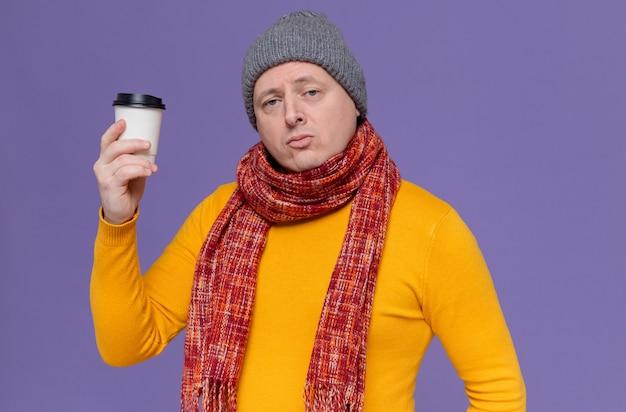 Selbstbewusster erwachsener slawischer mann mit wintermütze und schal um den hals, der pappbecher hält