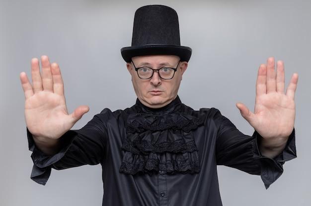 Selbstbewusster erwachsener slawischer mann mit zylinder und optischer brille in schwarzem gothic-hemd, der seine hände ausstreckt und stoppschild gestikuliert