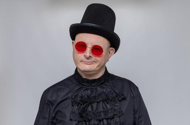 Selbstbewusster erwachsener slawischer mann mit zylinder und sonnenbrille im schwarzen gothic-hemd