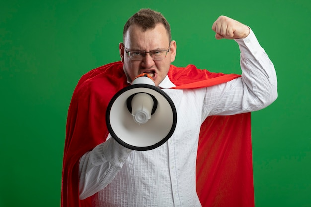 Selbstbewusster erwachsener slawischer superheldenmann im roten umhang, der brille tut, die starke geste tut, die durch sprecher spricht, der auf grüner wand lokalisiert wird