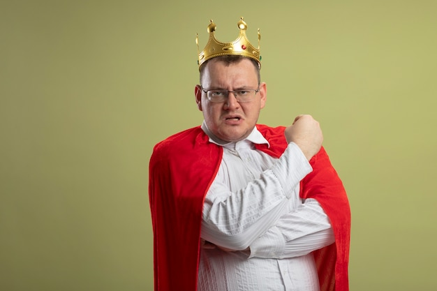 Selbstbewusster erwachsener superheldenmann im roten umhang, der brille und kronen-geballte faust trägt, die vorne lokalisiert auf olivgrüner wand betrachtet