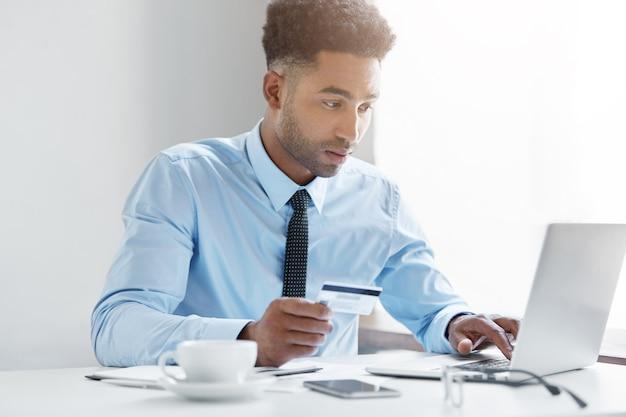 Selbstbewusster geschäftsmann, der an seinem laptop arbeitet