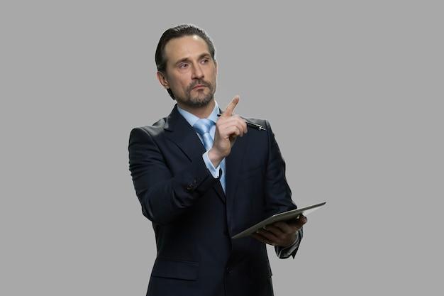 Selbstbewusster geschäftsmann, der digitales tablett verwendet. reifer männlicher designer im geschäftsanzug, der eine notiz auf pc-tablette gegen grauen hintergrund macht.