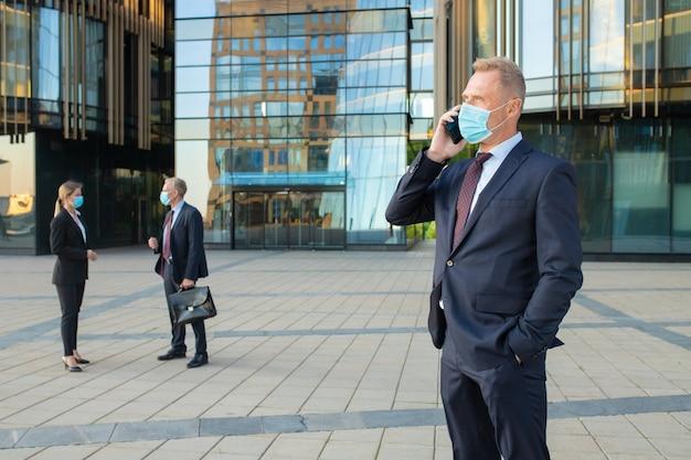 Selbstbewusster geschäftsmann, der maske und büroanzug trägt, die auf handy draußen sprechen. geschäftsleute und stadtbauglasfassade im hintergrund. speicherplatz kopieren. geschäfts- und epidemiekonzept
