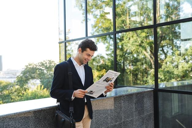 Selbstbewusster geschäftsmann, der zeitung liest, während er draußen steht