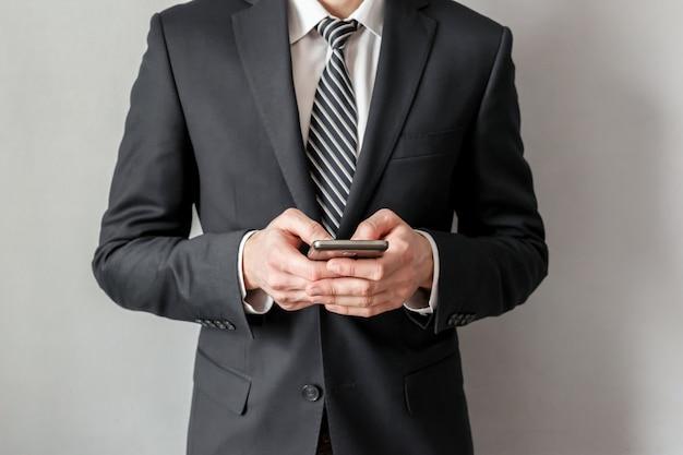 Selbstbewusster geschäftsmann im anzug, der nachricht an seinem smartphone schreibt.
