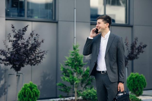Selbstbewusster geschäftsmann im klassischen anzug, der auf smartphone spricht und in straße geht. junger geschäftsmann, der geschäftsgespräch hat.